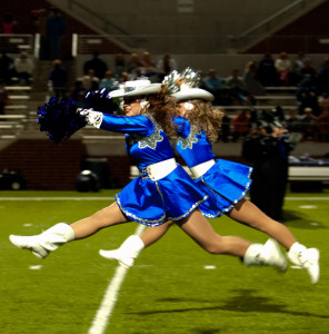 Dance team members performing for half-time show, fits the genre.